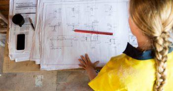 Ouvrière qui consulte les plans de construction d'un plateau brut