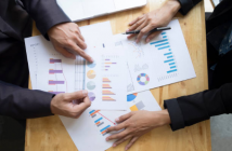 deux personnes avec documents graphiques statistiques sur une table