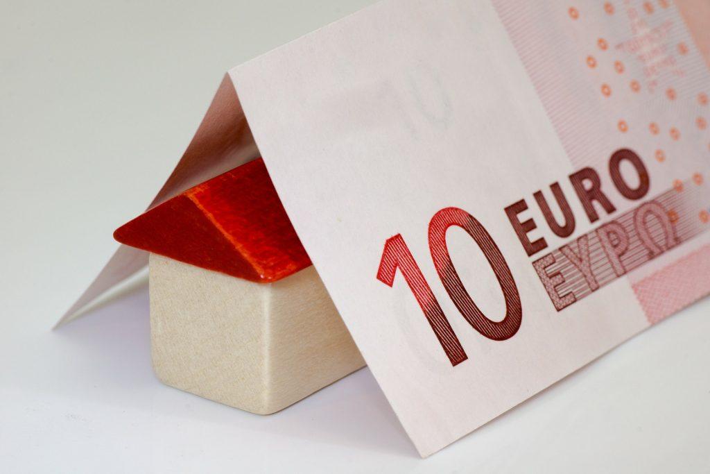 Maison miniature sur laquelle repose des billets en euros