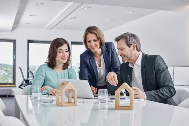 Trois personnes qui discutent autour d'un bureau, avec des maquettes de maisons en bois