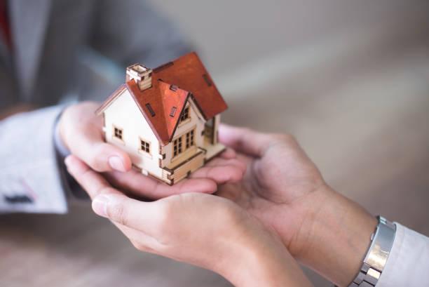 Mains d'une personne qui confie une petite maison en bois à une autre