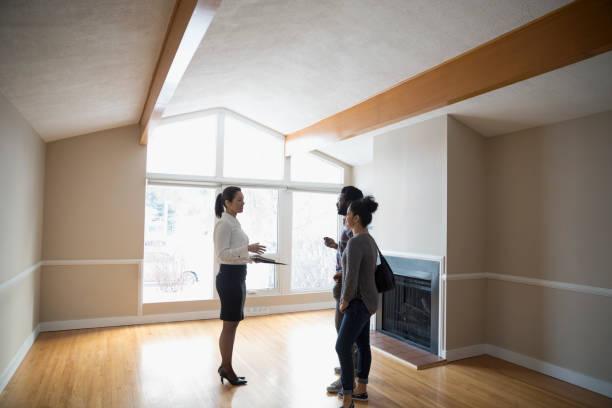 Une agent immobilier qui présente un bien à un jeune couple