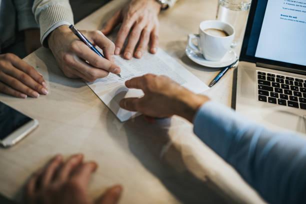 Une personne qui signe un contrat qu'un homme lui tend