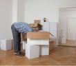 personne penchée la tête dans des cartons de déménagement