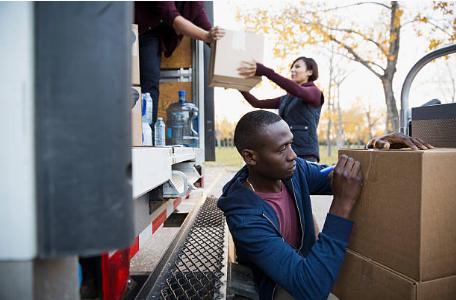 personnes chargeant et déchargeant des cartons de déménagement d'un camion