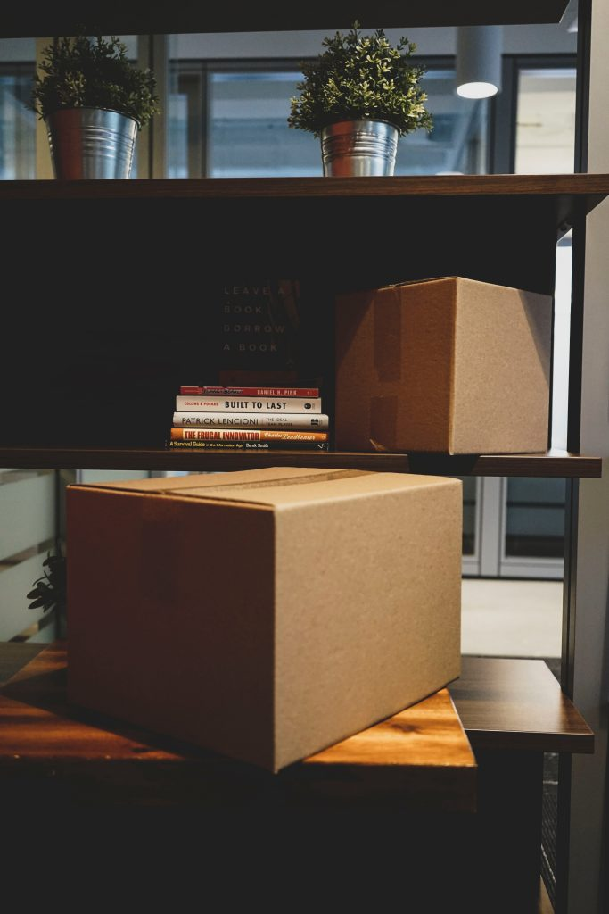 Cartons de déménagement posés sur une table basse et sur une étagère de livres